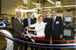 Ken Pulskamp, Ed Masterson, Jennifer Baldwin, Jeff Lage, Fred Duncan cut the ribbon in front of their new lean manufacturing cell.